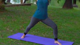 Den unga kvinnan som gör yoga, övar i ett tropiskt parkerar stock video