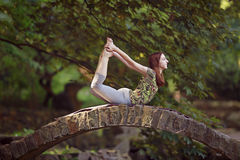 Den unga kvinnan som gör yoga, övar i park'sens bro Royaltyfria Foton