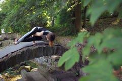 Den unga kvinnan som gör yoga, övar i park'sens bro Fotografering för Bildbyråer
