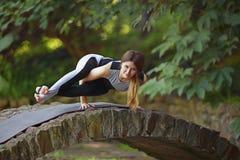 Den unga kvinnan som gör yoga, övar i park'sens bro Royaltyfria Bilder