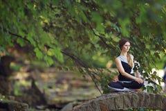 Den unga kvinnan som gör yoga, övar i park'sens bro Royaltyfri Foto