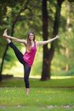 Den unga kvinnan som gör yoga, övar i park'sens gräsmatta Arkivbilder