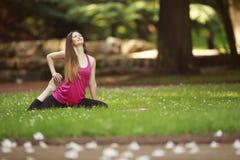 Den unga kvinnan som gör yoga, övar i park'sens gräsmatta Arkivfoton