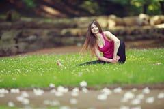 Den unga kvinnan som gör yoga, övar i park'sens gräsmatta Arkivbild