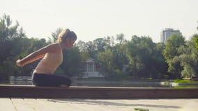 Den unga kvinnan som gör yoga, övar i parkera arkivfilmer