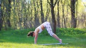 Den unga kvinnan som gör yoga, övar i sommarstaden parkerar Vård- livsstilbegrepp lager videofilmer
