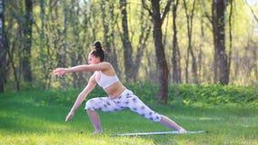 Den unga kvinnan som gör yoga, övar i sommarstaden parkerar Vård- livsstilbegrepp stock video