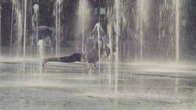Den unga kvinnan som gör yoga, övar inom springbrunnen stock video