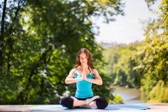 Den unga kvinnan som gör yoga, övar utomhus- arkivfoto