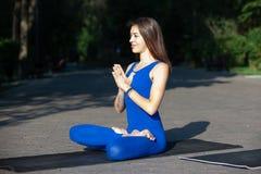 Den unga kvinnan som gör yoga i morgon, parkerar fotografering för bildbyråer