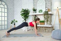 Den unga kvinnan som gör yoga i morgon, parkerar Arkivfoton