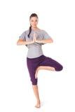 Den unga kvinnan som gör yogaasana, tree-poserar Arkivbilder