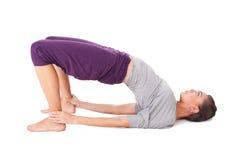 Den unga kvinnan som gör yoga, övar överbryggar poserar Royaltyfri Foto