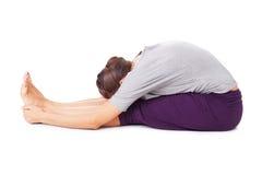Den unga kvinnan som gör yogaasana, placerade den framåt krökningen Paschimottanasa Arkivfoto