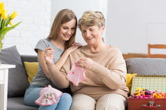 Den unga kvinnan som håller ögonen på hennes mormor, broderar Royaltyfria Bilder