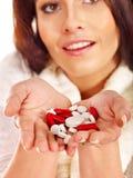 Den unga kvinnan som har influensa, tar preventivpillerar. Arkivfoton