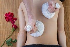Den unga kvinnan som har massage med den växt- kompressen, klumpa ihop sig i brunnsort royaltyfri foto