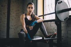 Den unga kvinnan som har något, vilar efter hård genomkörare i idrottshall Arkivfoto