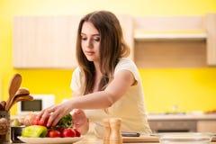 Den unga kvinnan som hemma förbereder sallad i kök arkivbilder