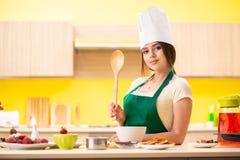 Den unga kvinnan som hemma förbereder sallad i kök royaltyfri fotografi