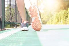Den unga kvinnan som joggar i, parkerar i morgonen under varm sunlig arkivbilder