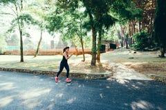 Den unga kvinnan som joggar på, parkerar royaltyfria foton