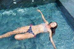 Den unga kvinnan som kopplar av i simbassängen med ögon, stängde sig Arkivbilder