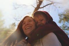 Den unga kvinnan som kramar den lilla sonen som in spelar, parkerar Arkivbild
