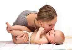 Den unga kvinnan som kysser henne, behandla som ett barn sonen Royaltyfri Fotografi