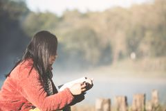 Den unga kvinnan som läser en bok i naturen, parkerar med friskhet Arkivfoton