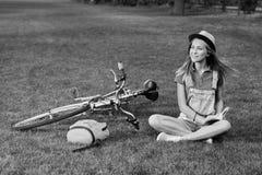 Den unga kvinnan som läser en bok, når han har cyklat på lokalen, parkerar fotografering för bildbyråer