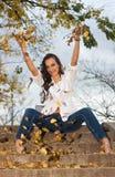 Den unga kvinnan som leker med guling, lämnar Royaltyfri Foto