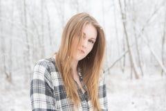 Den unga kvinnan som ler att stå i snö, täckte skogen Arkivbild