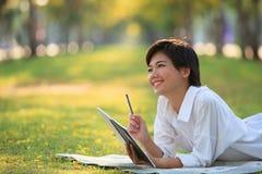 Den unga kvinnan som ligger på grönt gräs, parkerar med blyertspennan och anmärkningsboken Fotografering för Bildbyråer