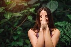 Den unga kvinnan som mediterar och gör yogaövning i tropiskt, parkerar Royaltyfri Foto