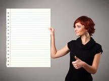 Den unga kvinnan som pappers- hållande vit kopierar utrymme med diagonalen, fodrar Royaltyfri Bild
