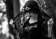 Den unga kvinnan som poserar i svart, snör åt klänningen royaltyfria bilder