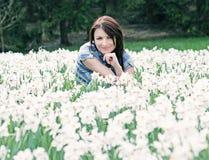 Den unga kvinnan som poserar med vita påskliljor, blått filtrerar Fotografering för Bildbyråer