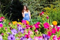Den unga kvinnan som poserar på bakgrunden, förgrunden, blommar Royaltyfri Bild