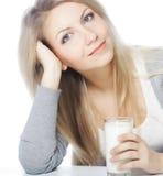 Den unga kvinnan som rymmer ett exponeringsglas av nytt, mjölkar Royaltyfri Foto