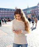 Den unga kvinnan som ser den smarta mobiltelefonen i PlazaborgmästareMadrid känsla, förlorade att söka efter riktningar royaltyfri fotografi