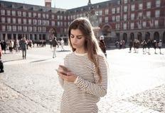 Den unga kvinnan som ser den smarta mobiltelefonen i PlazaborgmästareMadrid känsla, förlorade att söka efter riktningar fotografering för bildbyråer
