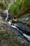 Den unga kvinnan som sitts på, vaggar att se en vattenfall Fotografering för Bildbyråer