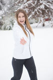Den unga kvinnan som skrattar och kastar, kastar snöboll Arkivfoto