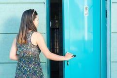 Den unga kvinnan som skriver in den offentliga toaletten utanför i, parkerar arkivfoto