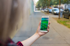 Den unga kvinnan som spelar Pokemon, går utomhus- Arkivbilder