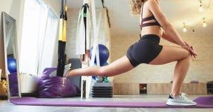 Den unga kvinnan som sträcker hennes ben i en yogastudio som använder en sakkunnig som stöttar har hon, en sunt livsstil och bära stock video