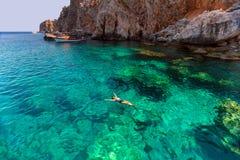 Den unga kvinnan som svävar i turkosfrikänd, bevattnar att koppla av och att bada i den Antalya fjärden på solig dag arkivfoton