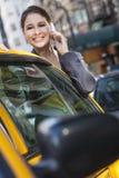 Den unga kvinnan som talar på celltelefonen vid Yellow, taxar Arkivfoton
