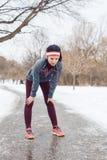 den unga kvinnan som tar ett avbrott, når han har joggat utanför i vinter, parkerar arkivbilder